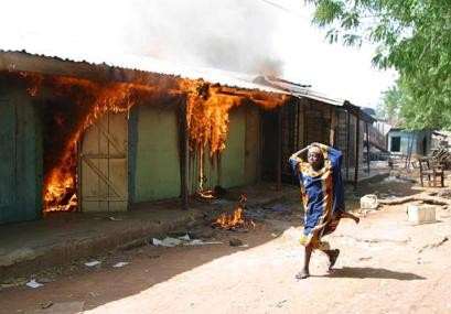 An unidentified girl runs past a building allegedly set ablaze by Christians following continuing fighting between Christains and Muslims communities in Yelwa north central BiafraNigeria, Wednesday, May 5, 2004.