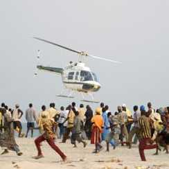 A crowd of bystanders run away as a police helicopter tries to land on a beach, near where a small plane crashed into the ocean, in Lagos, Nigeria, Friday Jan. 30, 2004.